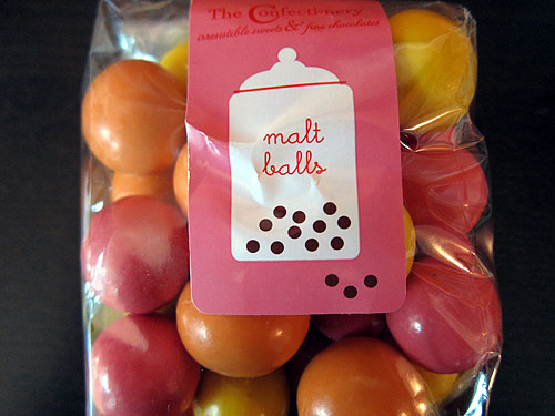 [a pack of pink, orange and yellow oversized malt balls]