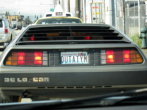 [a Delorean with the license plate OUTATYM]