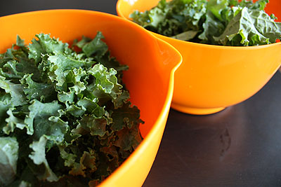 kale in orange bowls, ready to blanch