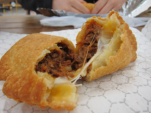 a fried pie, opened to show pot roast and cheese inside