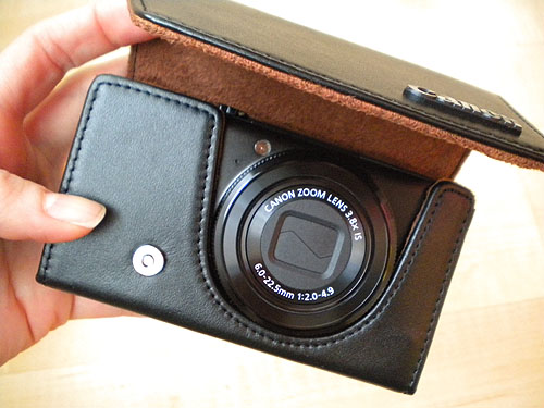 the Canon S90 camera nestled in a boxy leather case