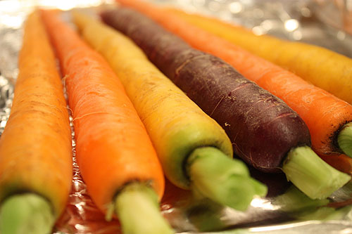 yellow, orange and purple carrots in a roasting pan