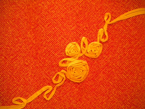 detail of ribbon detail on skirt, it is sewn down to form flowers