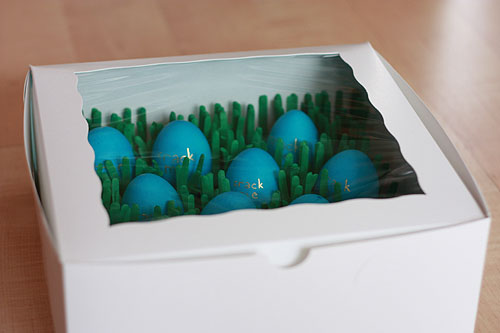 eggs nestled in tissue paper grass in a bakery box