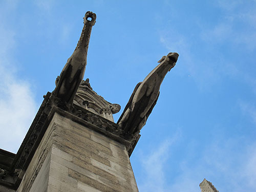 a Notre Dame gargoyle as seen from directly underneath, daylight showing through the mouth hole