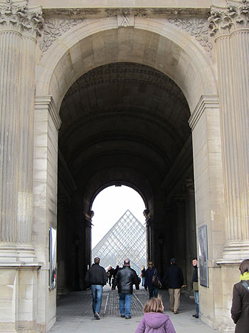 an entrance to the Louvre, with a pyramid showing through the arch