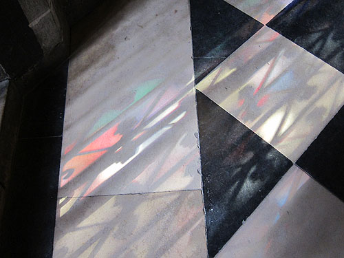 colored light on the floor that has come through a stained glass window