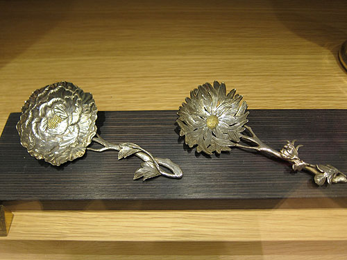 two serving spoons, both silver and formed to be flowers