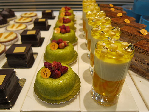 deserts on display at Pierre Herme, one is a layered jelly treat, topped with corn kernels and flecks of gold leaf