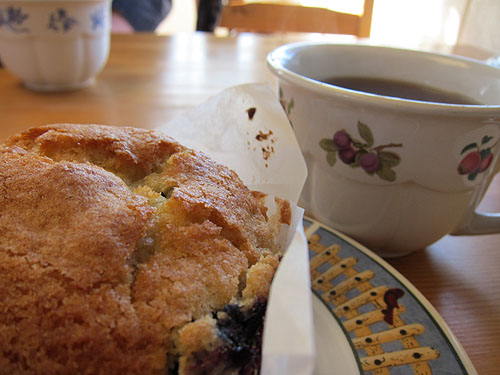 a blueberry muffin and coffee mug at Curio