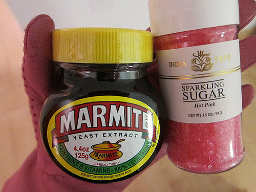 gloved hand holding Marmite and pink sugar