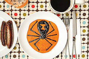 orange pancake with a spider image drawn in syrup
