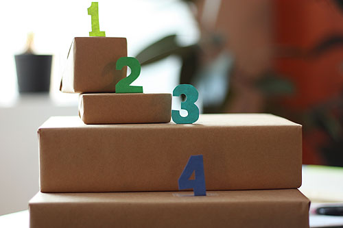 four boxes with colored paper numbers