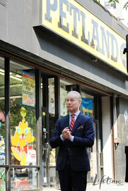 Tim Gunn in front of a pet supply store