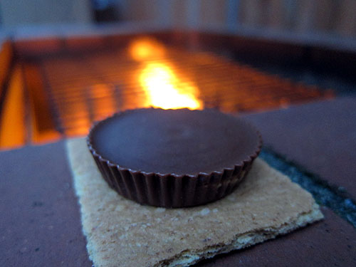 a peanut butter cup on a graham cracker warming by the fire