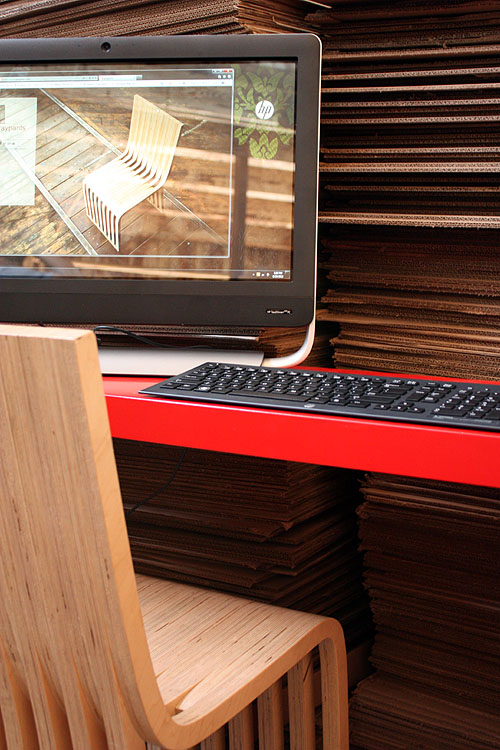 the HP TouchSmart on a red desk in front of a blue laser cutter and surrounded by stacks of cardboard