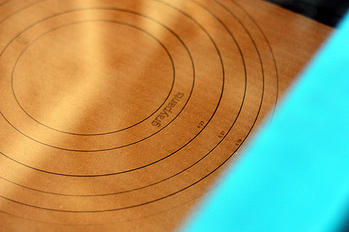 detail of the laser cutter slicing rings for a lampshade into cardboard and including an itty bitty graypants logo